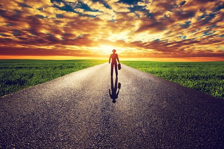 horizons: Man with suitcase and hat on long straight road towards sunset sky. Travel, business, destination, adventure concepts. Stock Photo