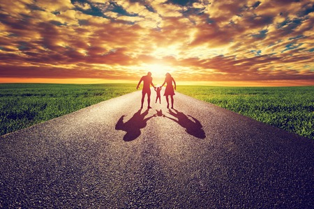 Family walk on long straight road, way towards sunset sun. Mother, father and child. Parenthood concepts