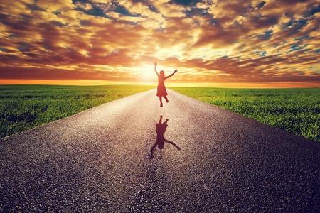 Donna felice che salta sulla lunga strada dritta, via verso il tramonto sole. Concetti Viaggi, felicità, vittoria, stile di vita sano. Archivio Fotografico - 38961500
