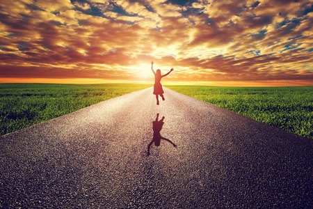 Happy woman jumping on long straight road, way towards sunset sun. Travel, happiness, win, healthy lifestyle concepts.