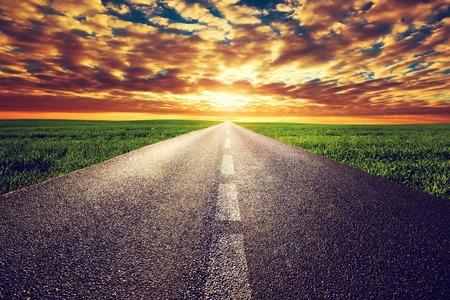 Long straight road, way towards sun. Sunset sky, travel, transport, destination concepts.