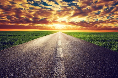 long way: Long straight road, way towards sun. Sunset sky, travel, transport, destination concepts.