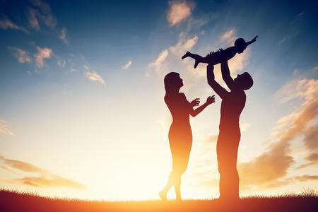 Familia feliz junto, los padres con su pequeño hijo en la puesta del sol. Padre levantar bebé en el aire.