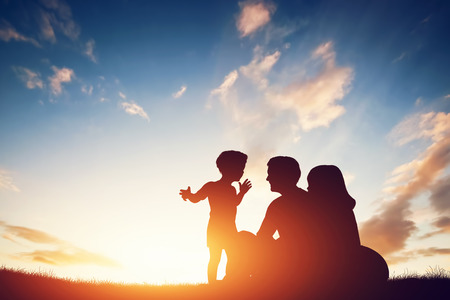 Happy family together, parents with their little child sitting on grass at sunset Standard-Bild
