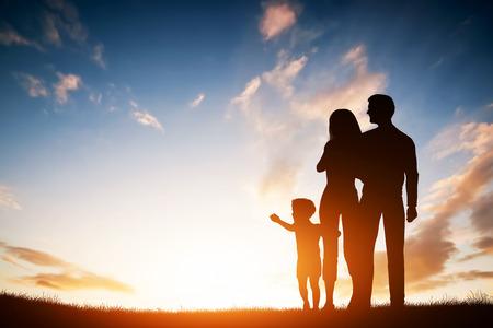 Счастливая семья вместе, родители с их маленьким ребенком на закате. Мальчик достижении солнце