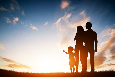 Happy family together, parents with their little child at sunset. Boy reaching the sun Stock Photo