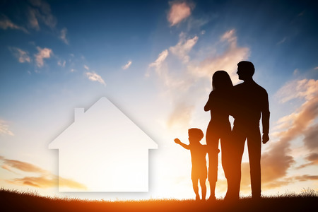 family on grass: Family dream about a new house, home. Child reaching for a dream with parents. Sunset sun, sky.