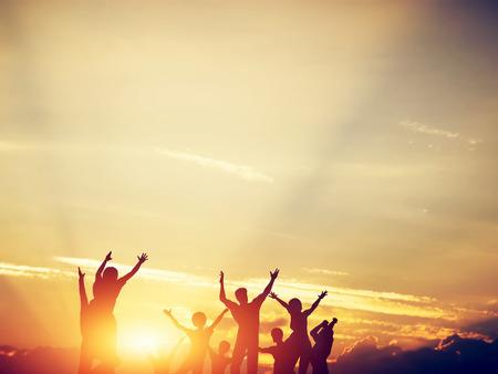 gente exitosa: Amigos felices, familia saltar juntos en un círculo que se divierten y expresar emociones de alegría, la libertad, el éxito. Siluetas en el cielo soleado