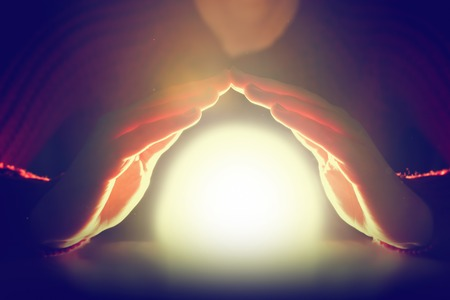 Vrouw houdt haar handen over gloeiende bol van licht. Bescherming, waarzegster, toekomst, magie, spiritueel concept. Stockfoto