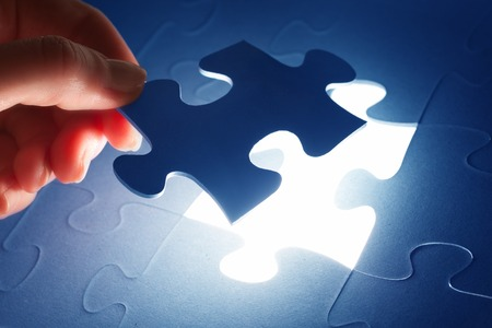 Completing the last piece of jigsaw puzzle. Light glow from empty space. Search for the solution, solving the problem, answer, business connection concept. Stock Photo