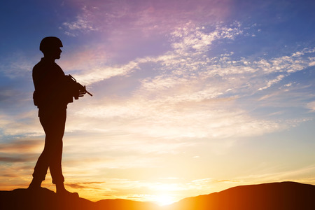mision: Soldado armado con el rifle de pie y mirando el horizonte. Silueta al atardecer. Guerra, ej�rcito, militar, guardia Foto de archivo
