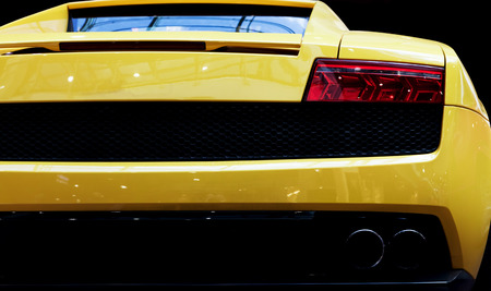 super car: Modern fast car close-up background. Luxury, expensive, sports auto. Rear view.