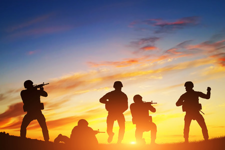 armed services: Soldiers in assault shooting with weapon, rifle at sunset. War, army, military. Stock Photo