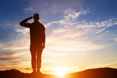 american soldier: Soldier salute. Silhouette on sunset sky. War, army, military, guard concept. Stock Photo