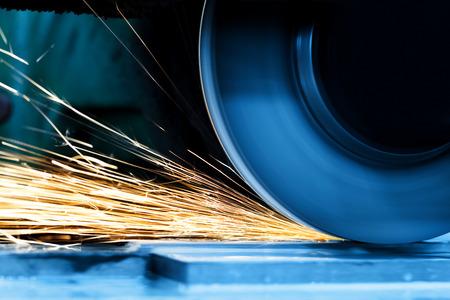 Vonken van slijpmachine in de werkplaats. Industriële achtergrond, industrie. Stockfoto