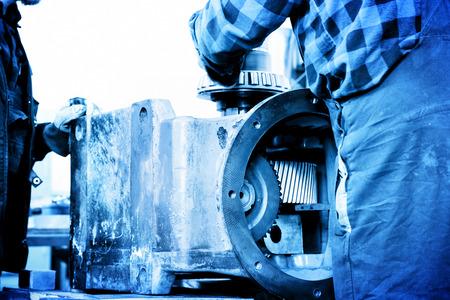 mechanical men: Workers repair, work on old gear element in workshop. Industry, industrial concept.