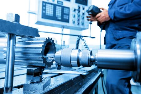maquinaria pesada: Hombre operativo de perforación CNC y máquina perforadora en el taller. Industria, concepto industrial. Foto de archivo