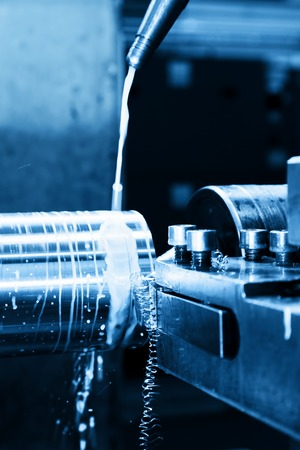 Industrial turning machine at work close-up. Industry concept, blue tone.