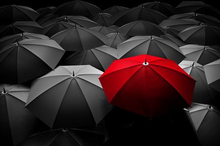 Красный зонт выделиться из толпы многих черно-белых зонтиков Фото со стока