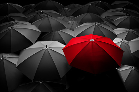 Red umbrella stand out from the crowd of many black and white umbrellas Foto de archivo