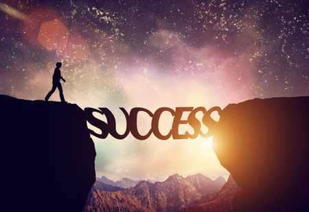Man about to walk over a precipice on the word SUCCESS bridge Stock Photo