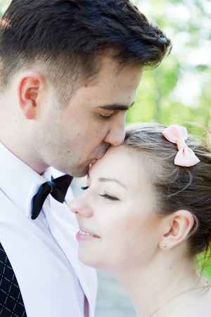 women subtle: Young handsome man embracing and gently kissing his fiancee outdoors. Date, fiance with fiancee, couple in love. Stock Photo
