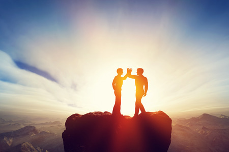 Two men, friends high five on top of the mountains. Agreement, positive energy, friendship concepts. Sunset sun light.