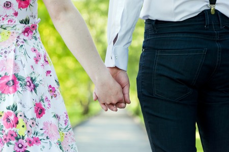 fiance: Young couple in love holding hands in summer park. Woman in dress and man wearing elegant shirt. View from the back. Date, fiance with fiancee, hand in hand concepts Stock Photo