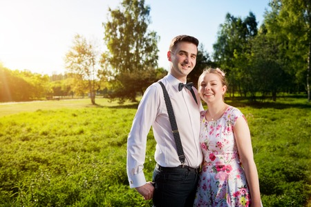 fiancee: Young couple in love portrait in summer park. Woman in dress and man wearing shirt with braces and bow tie. Looking at the camera. Date, fiance with fiancee concepts