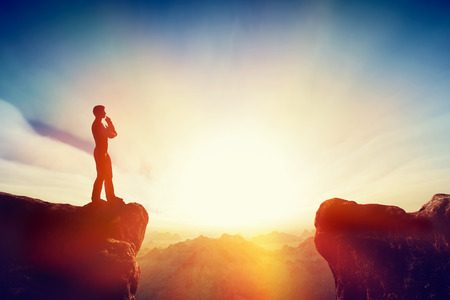 Solving the problem, thinking about solution, challenge concept. Man standing on mountain think about getting on the other side. Sunset sky, light.