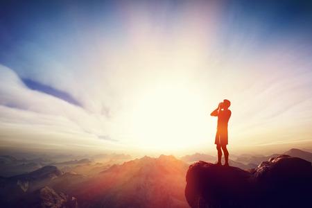 Mann schreiend auf dem Gipfel des mounain bei Sonnenuntergang. Konzept der Nachricht, um Hilfe zu rufen, etc.