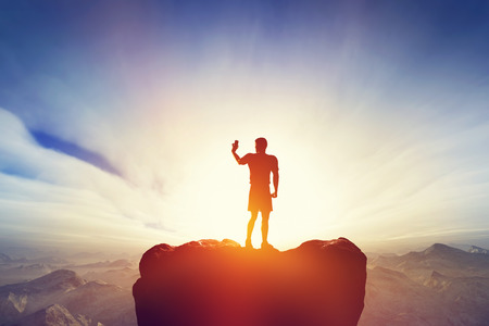 Man taking a picture or selfie with his smartphone, standing on the peak of the mountain. Mobile photography, modern media, technology concepts.