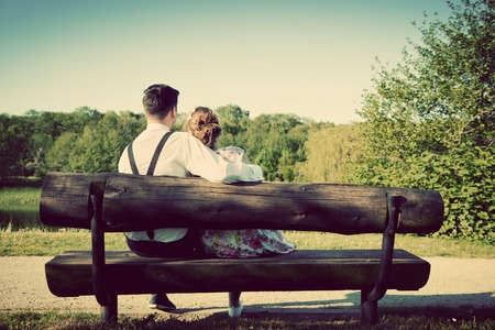sitting on bench: Young couple in love sitting together on a bench in summer park. Man wearing shirt with suspenders. Happy future, marriage concepts. Vintage Stock Photo