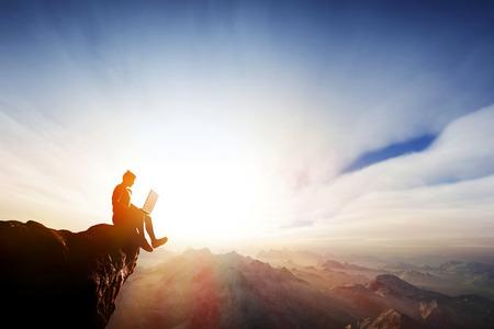 Man werkt op een notebook zitten op de rots op de top van de bergen. Concepten van een verblijf overal online, internet, vrijheid receptie etc.