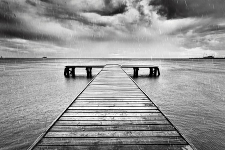 Old wooden jetty, pier on the sea. Raining from dramatic sky with dark, heavy clouds. Black and white Stock Photo