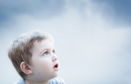 Boy looking at the sky with surprised expression. Imagination of a child Standard-Bild