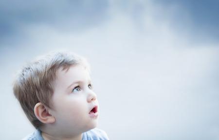 sorprendido: Muchacho que mira al cielo con expresión de sorpresa. La imaginación de un niño