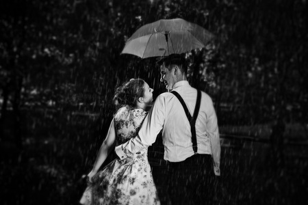 autumn rain: Young romantic couple in love flirting in rain, man holding umbrella. Dating, romance, black and white