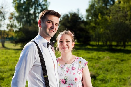 fiance: Young couple in love portrait in summer park. Woman in dress and man wearing shirt with braces and bow tie. Looking at the camera. Date, fiance with fiancee concepts