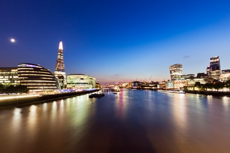 London skyline panorama at night, England the UK in lights. Moon shining. Tower of London, The Shard, City Hall, River Thames. Seen from Tower Bridge Editorial