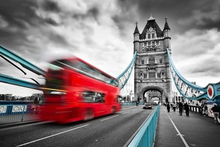 english bus: Bus rouge en mouvement sur Tower Bridge à Londres, au Royaume-Uni. Nuages ??pluvieux dramatique. Noir et blanc avec éléments de pont rouge et bleu.