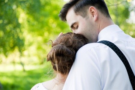 gently: Young handsome man embracing and gently kissing his fiancee in summer green park.  View from the back. Date, fiance with fiancee, couple in love.