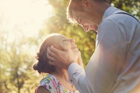 couple dating: Young romantic couple flirting in sunshine. Dating, love, romance, vintage flare. Stock Photo