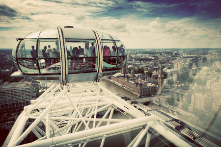 admiring: LONDON - JUNE 25: View from the London Eye capsule from its highest point on June 25 2015 in London, UK. People admiring the birds eye view on Big Ben and River Thames. Vintage filter applied