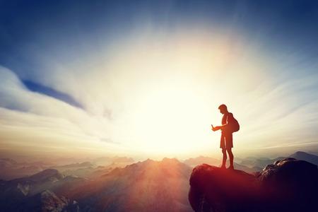 niño con mochila: Hombre que conecta con su teléfono inteligente en la parte superior de la montaña. Internet, la comunicación, los mensajes de texto del lugar conceptos remotas. Foto de archivo