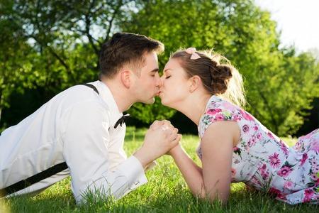 enamorados besandose: Pareja romántica en el amor besándose mientras está acostado en el césped en el parque de la primavera. Fecha de la vendimia, mujer en vestido y hombre llevaba tirantes con pajarita.