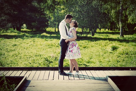 love park: Young couple in love standing on wooden cross-roads in summer park. Woman in dress and man wearing shirt with suspenders.