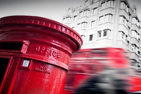 public service: Traditional red mail letter box and red bus in motion in London, the UK. Symbols of the city