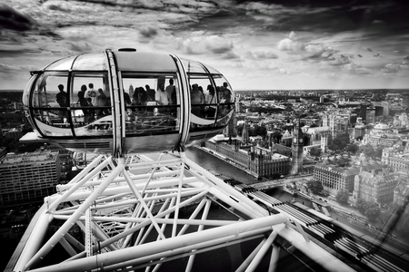 admiring: LONDON - JUNE 25: View from the London Eye capsule from its highest point on June 25 2015 in London, UK. People admiring the birds eye view on Big Ben and River Thames. Black and white