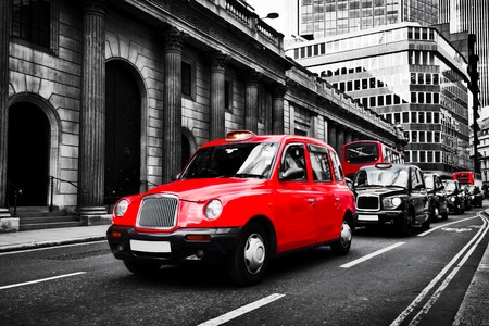 black and red: Symbol of London, the UK. Taxi cab known as hackney carriage.. Black and white with red. Iconic English transportation, red buses in the background